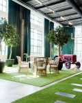 Stort rum med stora fönster inrett med växter, matgrupp och en traktor
